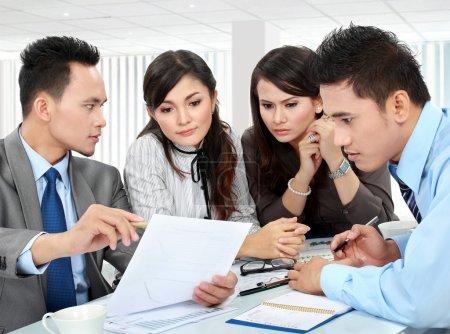 Photo pour Homme d'affaires et femme rencontre au bureau avec beaucoup de paperworks - image libre de droit