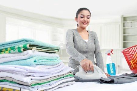Photo pour Joyeux jeune belle femme repassage vêtements - image libre de droit