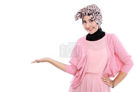 Photo pour Portrait d'une jeune femme musulmane montrant une zone vierge pour signe ou copyspace - image libre de droit