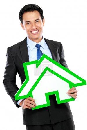 Portrait of businessman holding house sign