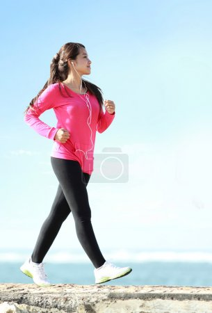 Photo for Happy healthy girl doing a brisk walking on the beach - Royalty Free Image