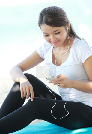 sporty young woman using cellphone