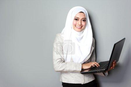 Photo pour Portrait de femme asiatique souriant tout en utilisant un ordinateur portable - image libre de droit