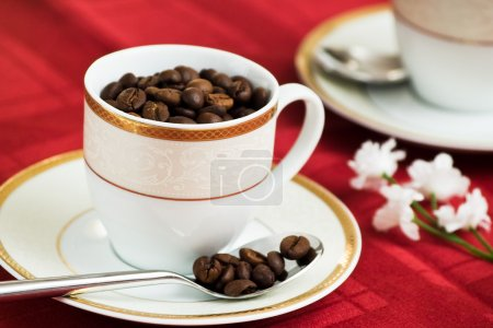 cup of coffee full of beans on red