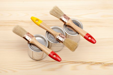 Cans of paint with paintbrushes isolated on white