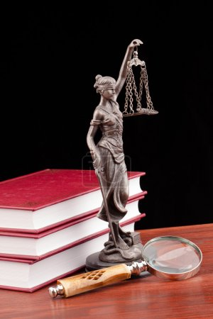 Law books, magnifying glass and lady of justice