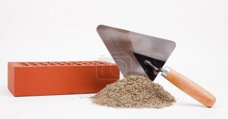 Mason trowel, brick and sand pile isolated on white
