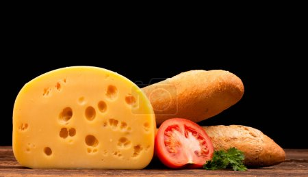 Block of cheese and bread isolated on black