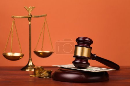 Judge gavel and scales of justice on table