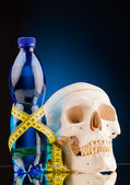 human skull and fitness dumbbells and bottle of water