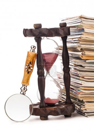 pile of newspapers and hourglass
