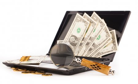 laptop computer keyboard money and magnifying glass