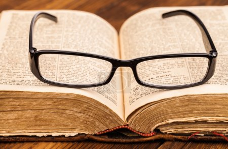 Reading glasses and old book