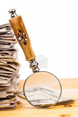 Photo pour Pile de journaux et loupe - image libre de droit