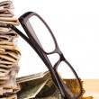 Pile of newspapers and reading glasses...
