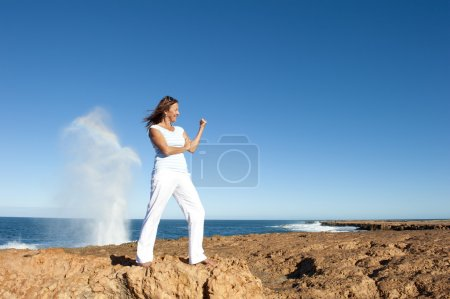 Strong and confident woman at ocean background