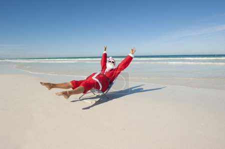Photo for Santa Claus happy relaxed sitting with hands up at beach, having fun and joy off duty at tropical holiday vacation, isolated with ocean and blue sky as background and copy space. - Royalty Free Image