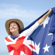 Portrait of Attractive mature woman wearing akubra hat and with Australian flag around shoulder posing isolated with blue sky as background and copy space.