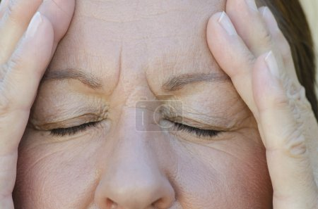 Photo for Close Up portrait of worried woman with closed eyes and hands on forehead. - Royalty Free Image