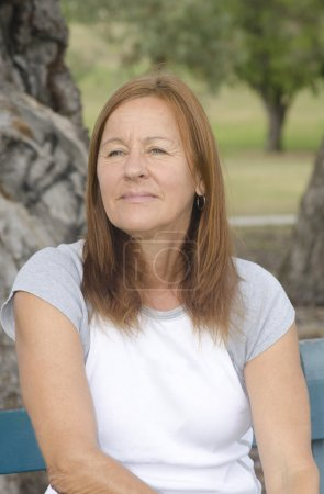 Photo for Sad and lonely looking middle aged woman sitting on park bench with worried or depressed facial expression and blurred background outdoor. - Royalty Free Image