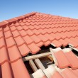 Damaged roof construction on house needs tiles or shingles repaired and replaced, red tiles and blue sky as background and copy space.