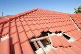 Damaged red tile roof construction house