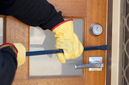 Burglar breaking in house with crowbar at door