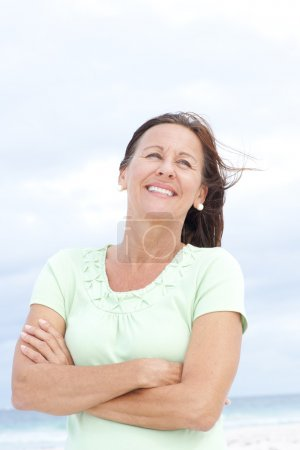Confident happy mature woman beach