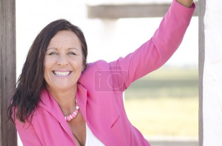 Photo for Portrait sexy mature woman with confident and happy smile, wearing elegant pink jacket, isolated on white and with blurred background - Royalty Free Image