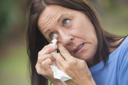 Sad mature woman tissue cleaning tears in eye