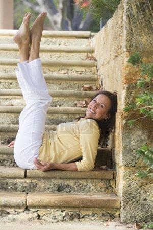 Photo pour Beau portrait, ajustement et saine femme mature assise confiant, détendu et heureux souriant avec jambes s'étendait vers le haut sur les étapes de calcaire dans le parc extérieur avec espace copie. - image libre de droit