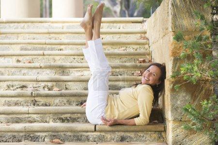 Photo pour Portrait attrayant, ajustement et saine femme mature assise confiant, détendu et heureux souriant avec jambes s'étendait vers le haut sur les étapes de calcaire dans le parc extérieur avec espace copie. - image libre de droit