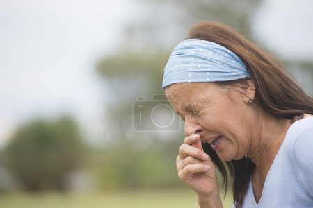 Sneezing woman with flu, hayfever or cold outdoor