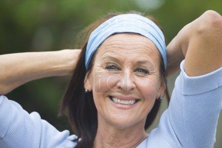 Photo pour Portrait attrayant regardant femme mature gai, joyeux heureux souriant en plein air, portant chemise bleue et bandeau, bras derrière le cou, fond flou . - image libre de droit