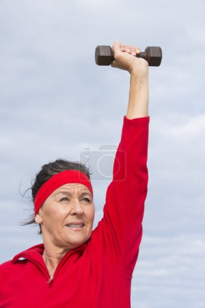 Energetic mature woman weights exercising