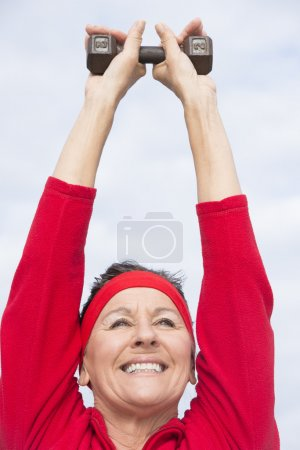Friendly healthy mature woman exercising