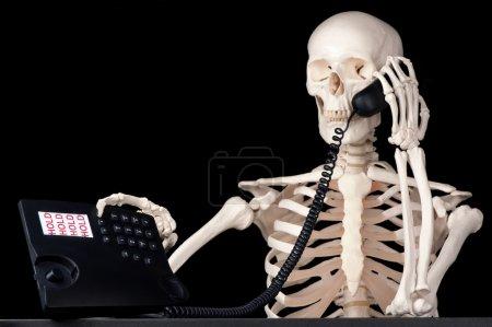 Photo pour Un employé de centre d'appel squelettique conserve un appel en attente pour toujours. - image libre de droit