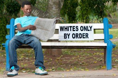 Photo pour Un homme non-blanc est assis sur un banc dans un parc réservé aux blancs. C'était monnaie courante pendant les années de l'apartheid en Afrique du Sud. - image libre de droit