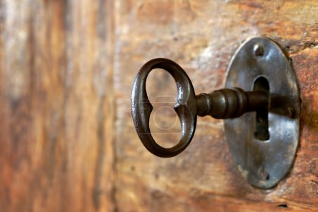 Photo for Closeup of an old keyhole with key on a wooden antique door - Royalty Free Image
