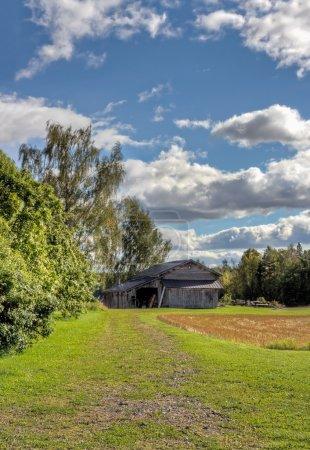 Photo pour Ancienne grange rustique avec ciel bleu et nuages, champ doré récolté - image libre de droit