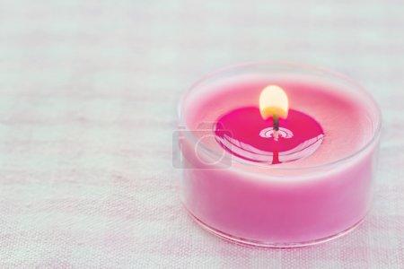 Pink burning candle on a romantic soft background