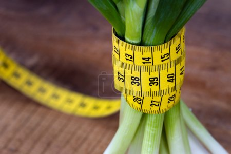 Photo for Green onions with yellow measurement tape on rustic wooden background; weight loss and diet concept - Royalty Free Image
