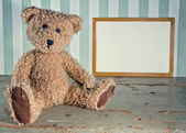 Antique teddy bear sitting next to an empty wooden frame