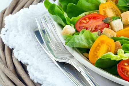 Photo for Green salad on a plate with tomatos and croutons - healthy lunch with rustic table setting - Royalty Free Image