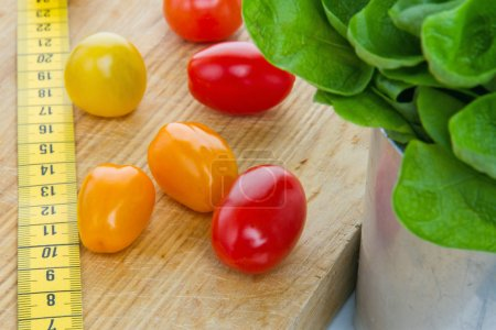 Photo for Salad, tomatos and measurement tape - diet and healthy eating; weight loss concept - Royalty Free Image