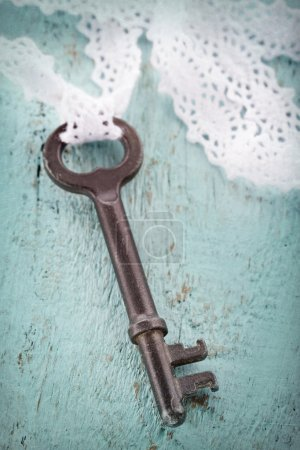 Old metal key with romantic white lace