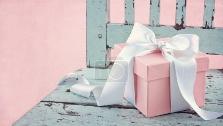 Photo for Pink romantic gift box with white satin bow on a light blue wooden chair - Royalty Free Image