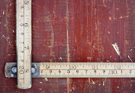 Old meter stick on old wooden background