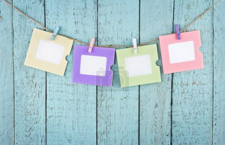 Four empty photo frames hanging with clothespins