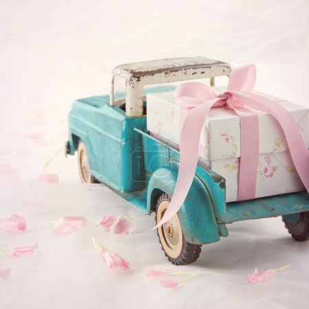 Old antique toy truck carrying a gift box with pink ribbon